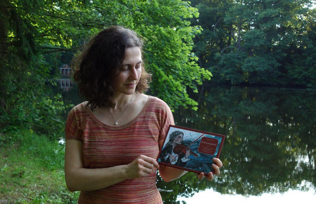 """Marlene Hofmann mit Buch """"Wasserspiele"""" am Teich in Nöbdenitz, der in einer der Kurzgeschichten vorkommt."""